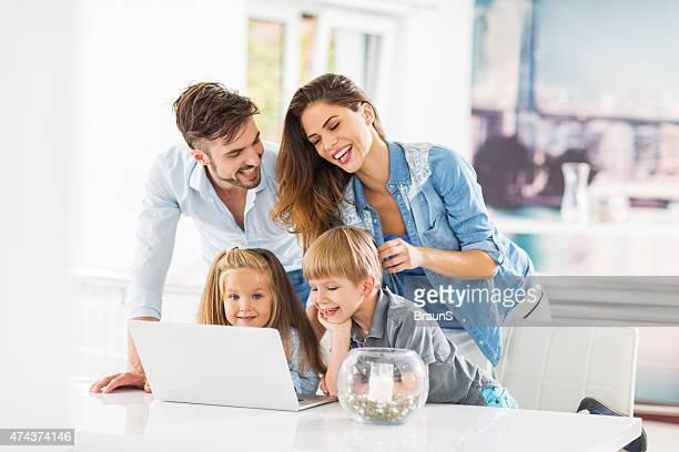 Giovani genitori insegnare i bambini piccoli come utilizzare un computer portatile.