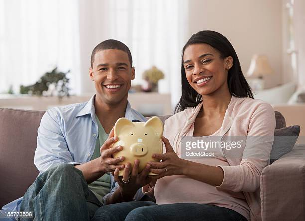Young parents to be holding piggy bank