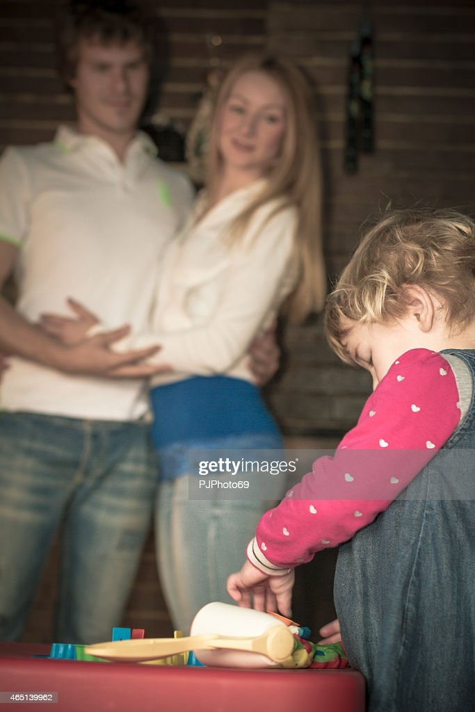 Young parents watching her daughter playing : Stock Photo
