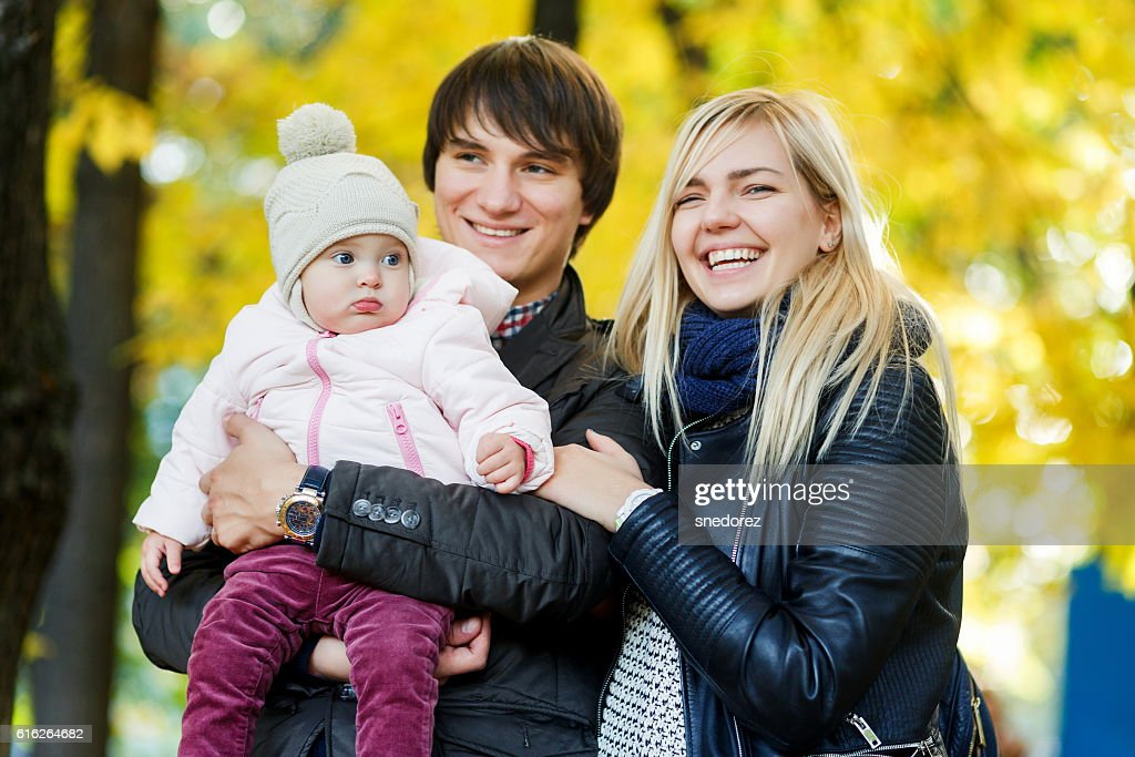 Young parents with baby in autumn park among trees : Stock Photo