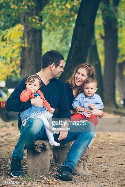 young parents with children in the park - cute twins stock photos and pictures