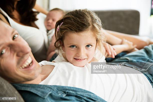 Young parents with male newborn and little daughter sitting on sofa at home