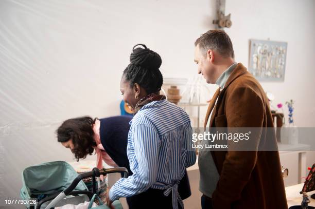 young parents with their baby, at creative pop up store - older woman bending over stock pictures, royalty-free photos & images