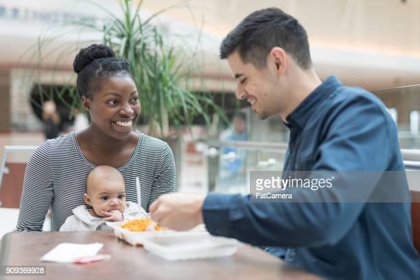 young parents with their baby eat lunch at a food court. - filipino family eating stock pictures, royalty-free photos & images