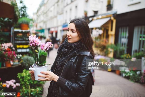 Jeune femme parisienne achat de fleurs sur le marché