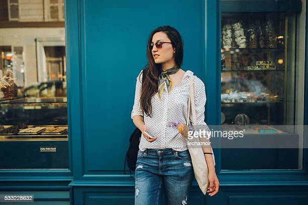 young parisian woman buying in a bakery - french culture stock pictures, royalty-free photos & images