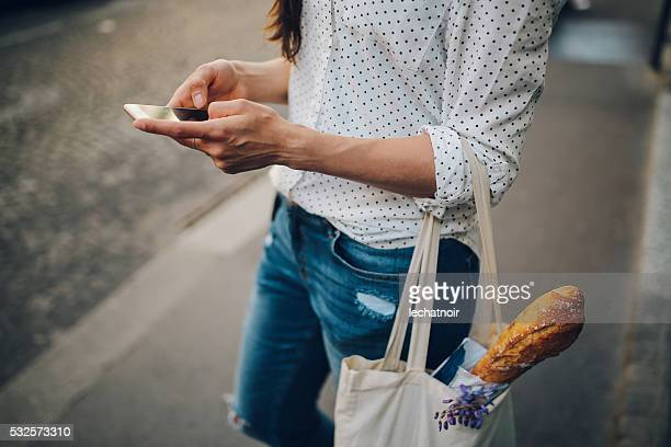 young parisian woman using the smartphone - franse cultuur stockfoto's en -beelden