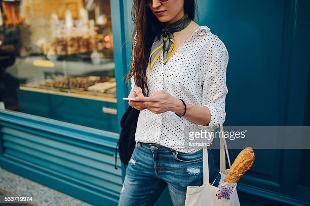 young parisian woman using the smartphone - spijkerbroek stockfoto's en -beelden