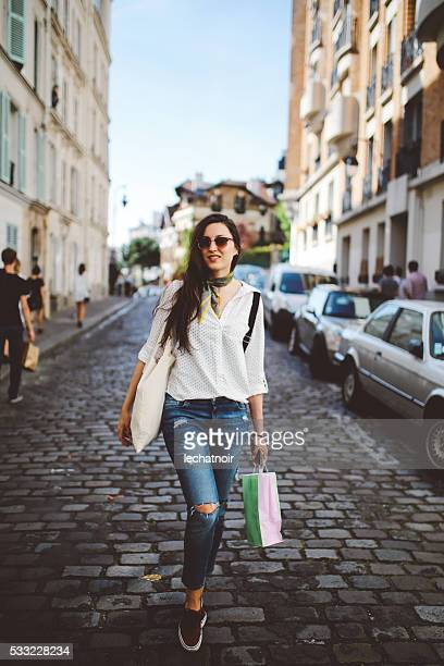 Young Parisian woman walking on Montmartre after shopping