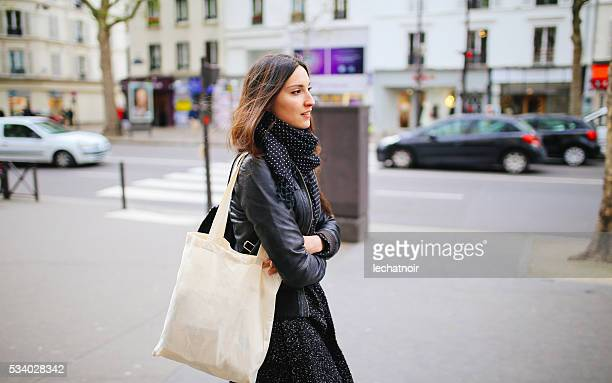 young parisian woman walking - shopping bag stock photos and pictures