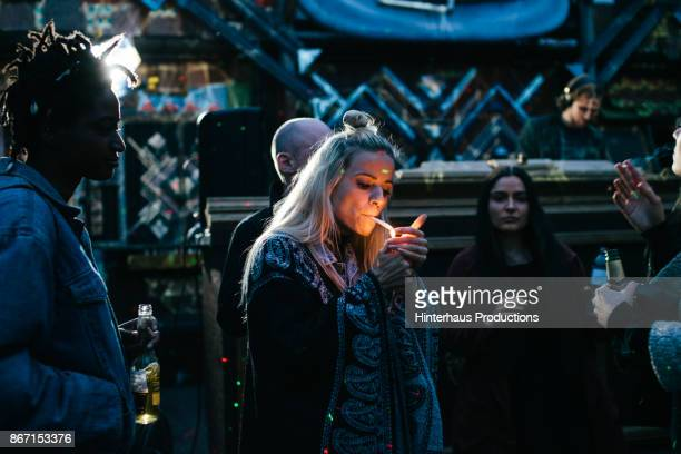 young partygoer lighting a joint while dancing with friends - femme qui fume photos et images de collection