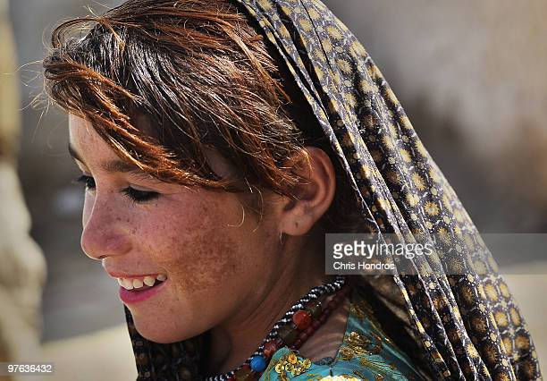 A young Pashtun girl watch smiles as US Marines hand out trinkets in her village March 11 2010 in a hamlet near Khan Neshin in Helmand Province...
