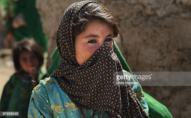 A young Pashtun girl watches as US Marines hand out trinkets in her village March 11 2010 in a hamlet near Khan Neshin in Helmand Province...
