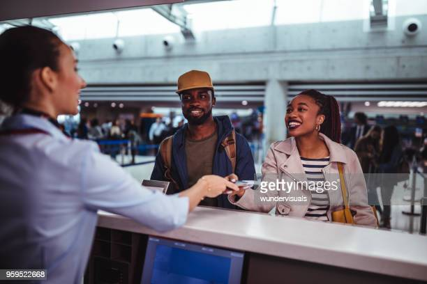 young passengers doing check-in for flight at airport - passenger stock pictures, royalty-free photos & images