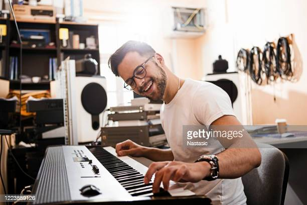 young passionate man playing electric piano - piano stock pictures, royalty-free photos & images