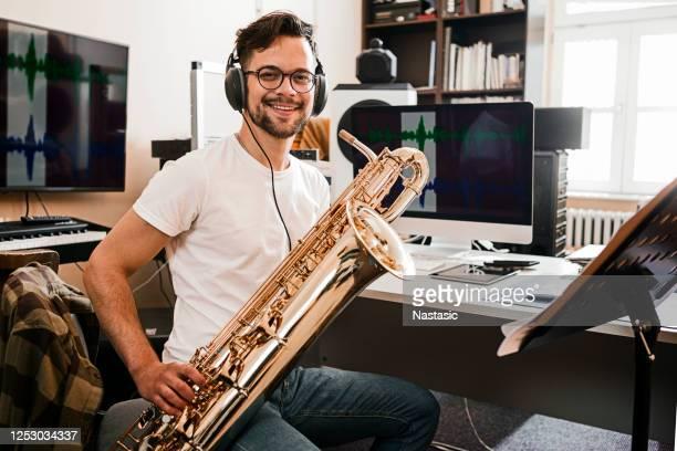 junger leidenschaftlicher mann spielt saxophon und schaut in die kamera - darstellender künstler stock-fotos und bilder