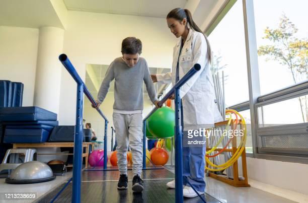 jonge patiënt die fysiotherapie bij een kliniek met hulp van een therapeut doet - sports uniform stockfoto's en -beelden