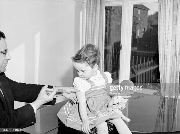 A young patient looks on with trepidation whilst having her polio vaccination circa April 1959