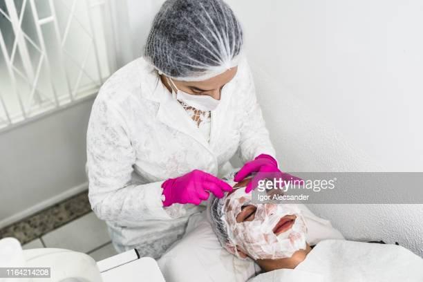 Junger Patient Mann während der Hautbehandlung für die Entfernung von Pickeln und Mitessern im Gesicht
