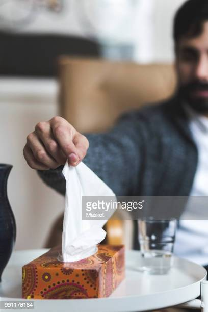 Young patient removing tissue from box at table