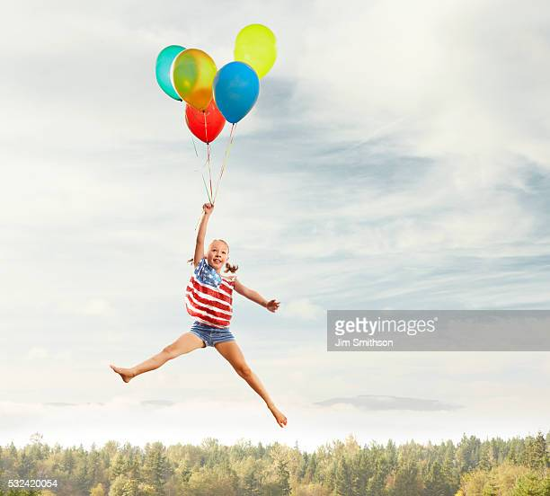 Young, patriotic girl clutching balloons seemingly floating in air