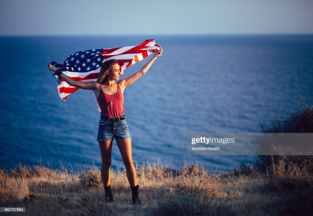 https://media.gettyimages.com/photos/young-patriotic-woman-holding-american-flag-by-the-sea-picture-id952737594
