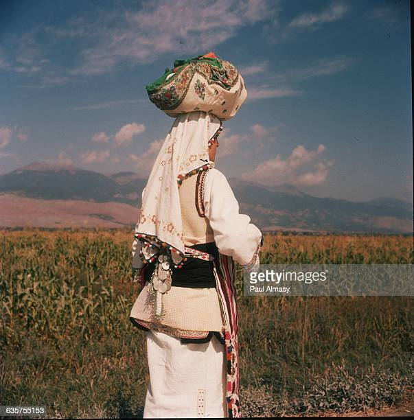 A young peasant girl wearing traditional dress carries a load on her head in Macedonia Yugoslavia