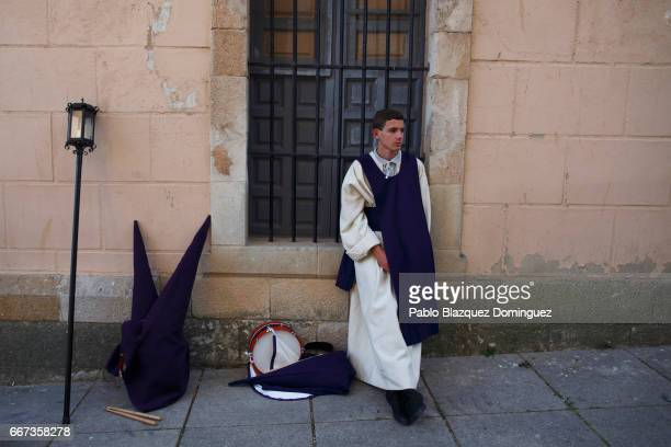 A young penitent from the Jesus del Via Crucis brotherhood leans on a window before taking part in a procession on April 11 2017 in Zamora Spain...