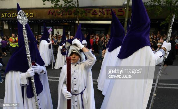 A young penitent removes his hood as he takes part in the Silence brotherhood procession during Holy Week celebrations in Madrid on April 18 2014...