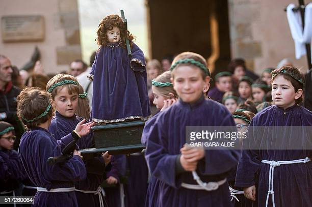 Young penitents carrying an effigy of Our Lady of Sorrow wait during a Holy Week procession in the northern Spanish Basque village of Segura on March...