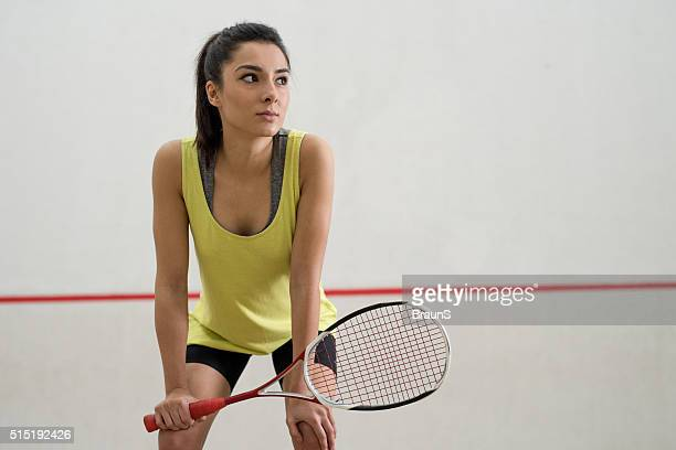 Young pensive athlete taking a break from racketball game.