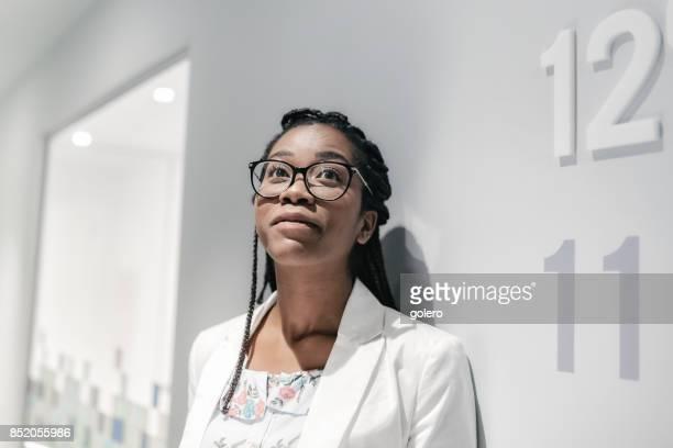 unga fundersam brasilianska affärskvinna tittar upp i office