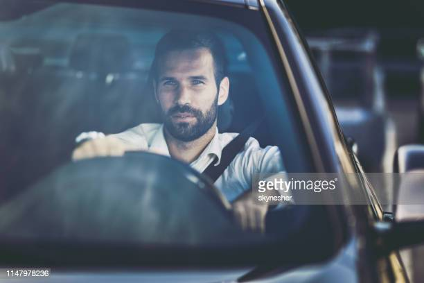 young pensive businessman driving a car. - windshield stock pictures, royalty-free photos & images