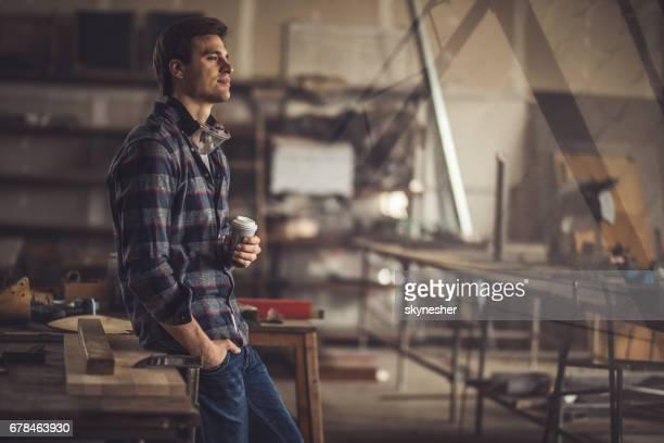 Nachdenkliche junge Tischler mit einer Kaffeepause in einem Workshop.