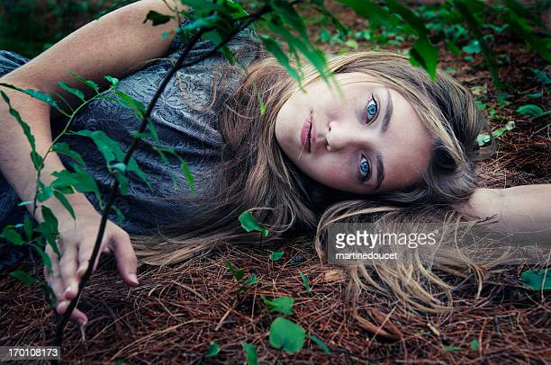 Young pensive woman lying on the ground.