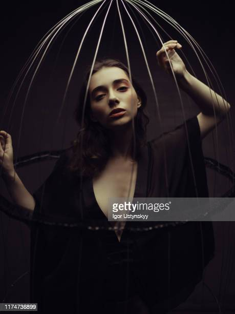 young pensive woman trapped in birdcage - woman prison stock-fotos und bilder