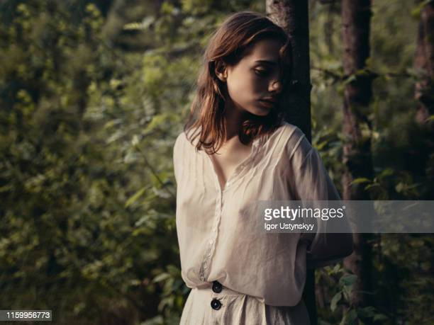 young pensive woman walking in forest - brustwarze stock-fotos und bilder