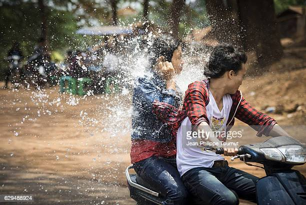 Young people after being splashed by a bucket of water while riding a motorbike on the road during Thingyan Water Festival, Myanmar's traditional New Year Festival, in April 2016