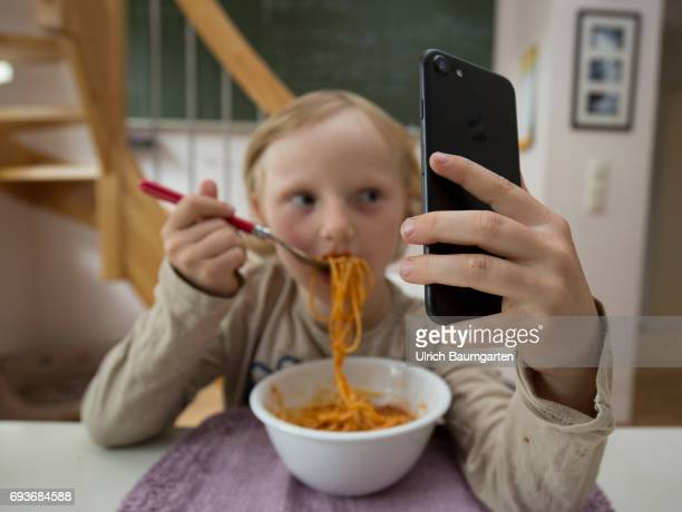 Young people and the dependence on electronic media The photo shows a young girl during her spaghetti meal completely distracted and fascinated by a...
