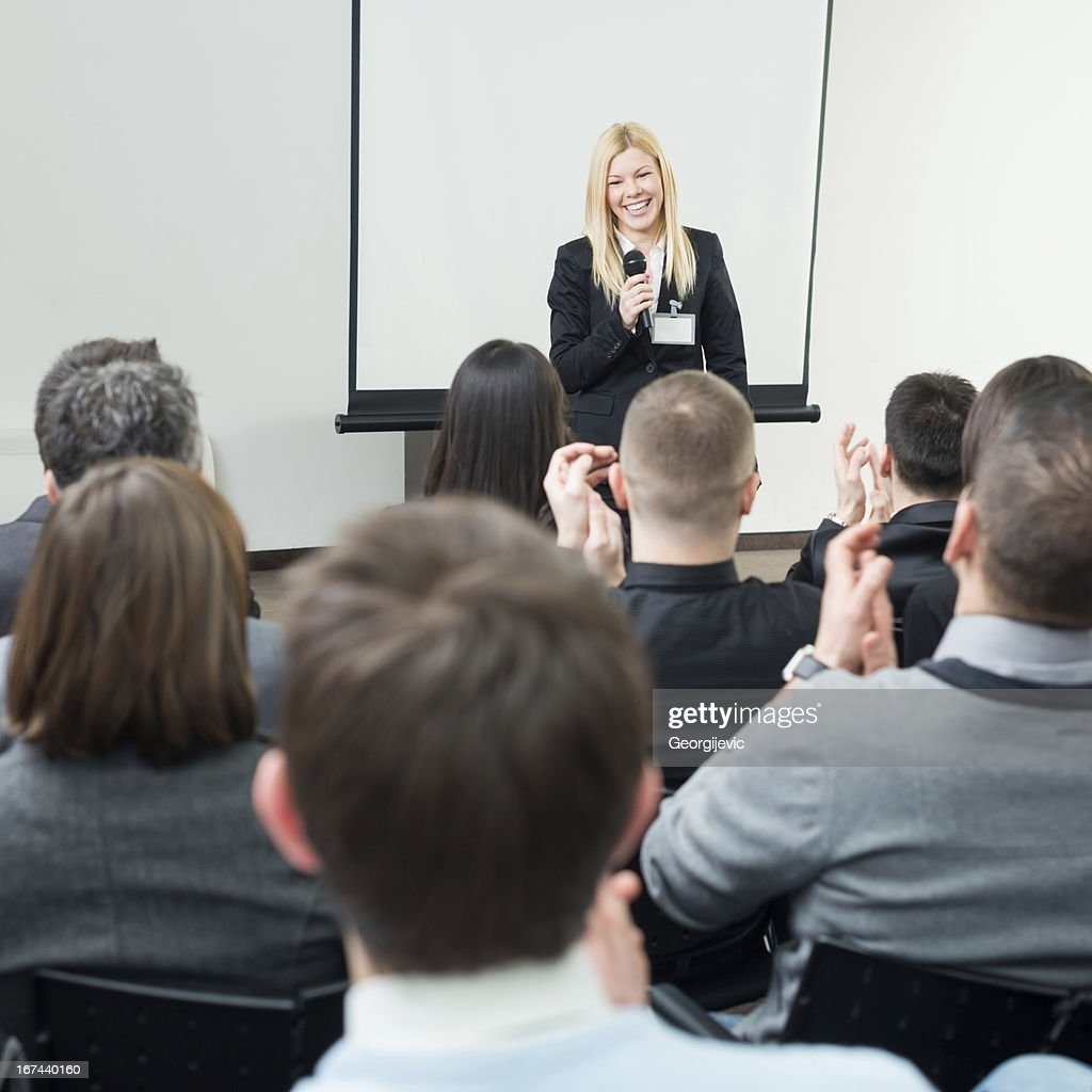 Young people applauding to a seminar presenter : Stock Photo