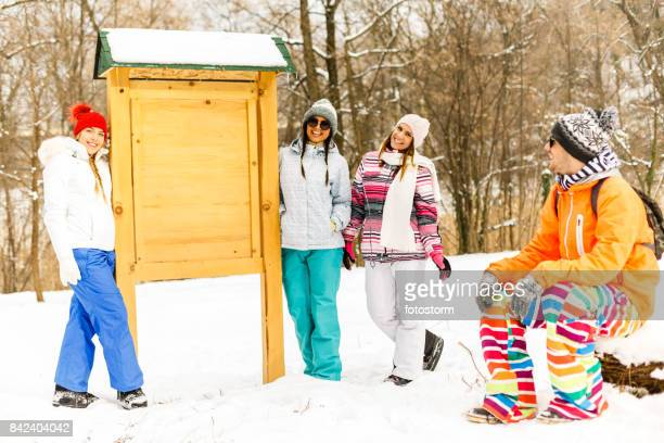 young people around the blank wooden board - ski pants stock pictures, royalty-free photos & images