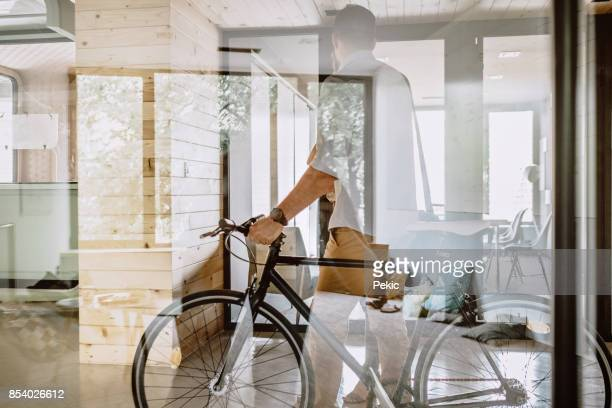 young people arriving at work with a bicycle - environmental conservation stock pictures, royalty-free photos & images