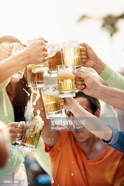 Los jóvenes en bistro con cerveza.