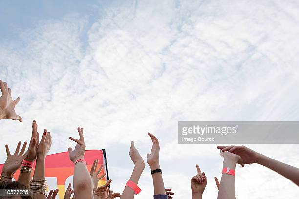 Young people at festival, arms raised