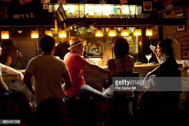 Young people at the bar in a cool edgy bar in Havana old town drinking and chatting in the low atmospheric lighting Havana Cuba