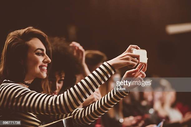 Young people at the concert, taking selfie using mobile