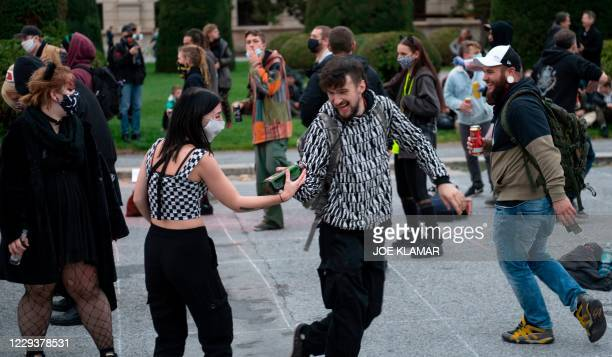 Young people attend a street party at Maria-Theresia square during a counter protest against the nearby demonstration aimed against Austrian...