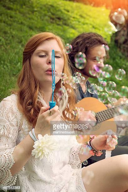 Junge Blasen Blasen und spielt Gitarre im park.