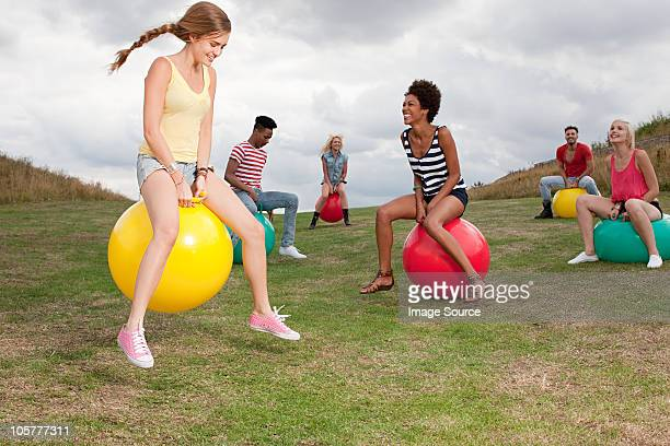 young people bouncing on hoppity horses - hoppity horse stock photos and pictures