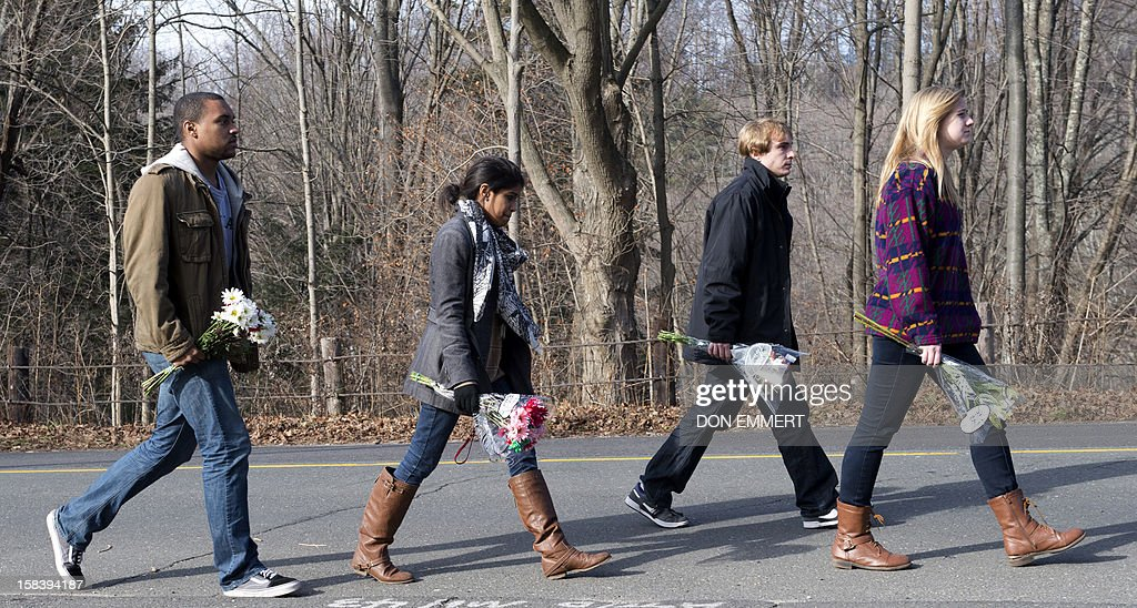 Young people carry flowers to leave near Sandy Hook Elementary